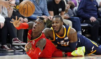 Atlanta Hawks guard Dennis Schroder, left, passes the ball as Utah Jazz forward Jae Crowder, right, defends in the second half during an NBA basketball game Tuesday, March 20, 2018, in Salt Lake City. (AP Photo/Rick Bowmer)