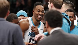 Charlotte Hornets center Dwight Howard celebrates with teammates after the Hornets' 111-105 defeat win over the Brooklyn Nets in an NBA basketball game Wednesday, March 21, 2018, in New York. (AP Photo/Kathy Willens)
