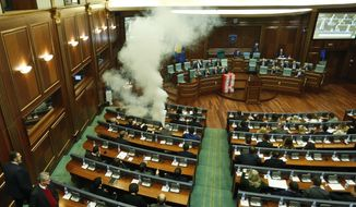 Opposition lawmakers release a tear gas canister disrupting a parliamentary session in Kosovo capital Pristina on Wednesday, March 21, 2018. Kosovo's Parliament, has temporarily suspended its session after tear gas disrupted the vote on a border demarcation deal with Montenegro. (AP Photo/Visar Kryeziu)
