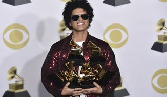 FILE - In this Jan. 28, 2018 file photo Bruno Mars poses with his awards at the 60th annual Grammy Awards in New York. The Weeknd, Bruno Mars, Jack White and Arctic Monkeys will headline this year's Lollapalooza music festival in Chicago. Travis Scott, The National, Vampire Weekend and Odesza also were among the headliners announced Wednesday, March 21, on Lollapalooza's website. (Photo by Charles Sykes/Invision/AP File)