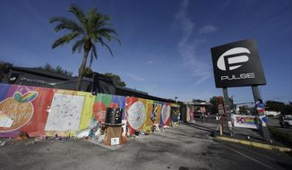 In this Nov. 30, 2016, file photo, artwork and signatures cover a fence around the Pulse nightclub, scene of a mass shooting, in Orlando, Fla.  Jurors in the federal trial of  Noor Salman, the Pulse nightclub gunman's widow, have gotten a look inside his Florida condo through crime scene photos taken as FBI agents searched the home. They also saw some of her husband Omar Mateen's web browsing history Tuesday, March 20, 2018, including beheading videos created by the Islamic State group Mateen had pledged allegiance to. Salman is accused of aiding and abetting her husband in the 2016 attack that left 49 people dead. (AP Photo/John Raoux)