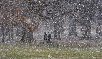 People cross Flagstaff Hill as the snow starts to fall, in Schenley Park, on their way to the Carnegie Mellon University campus, Tuesday, March 20, 2018, in the Oakland section of Pittsburgh. Yet another powerful storm bore down on the Northeast on Tuesday, with wind-whipped snow falling in parts of Pennsylvania and New Jersey as people grumbled and complained about a first day of spring that looked an awful lot like the last weeks of winter.  (Darrell Sapp/Pittsburgh Post-Gazette via AP)