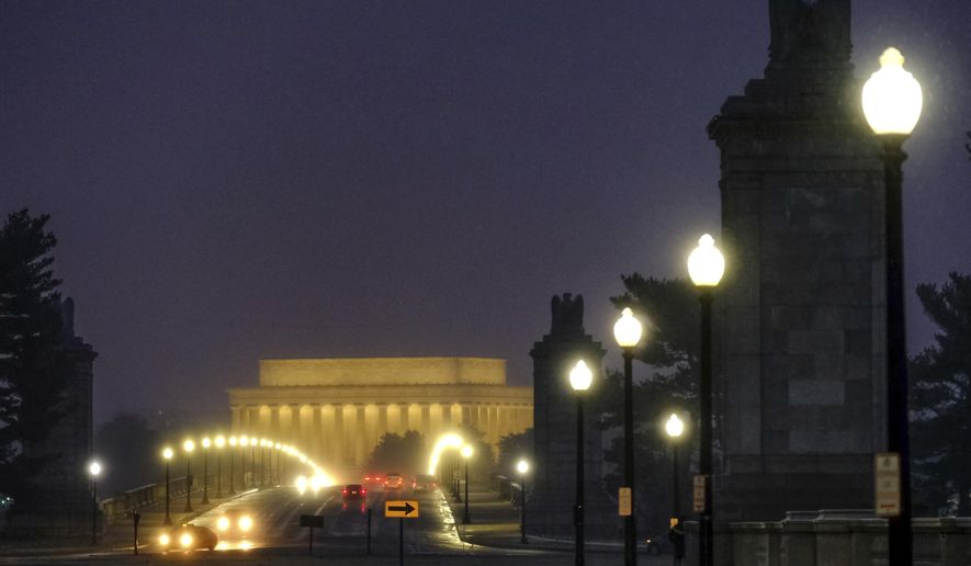 Traffic moves across the Memorial Bridge with the Lincoln Memorial in the background as snow begins to fall before daybreak in Washington, Wednesday, March 21, 2018. (AP Photo/J. David Ake)