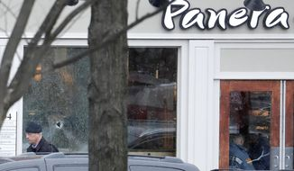 A hole is seen on a glass panel as a man leaves a Panera Bread restaurant in Princeton, N.J., where an armed man was holed up across the street from Princeton University's campus, Tuesday, March 20, 2018. Police say there are no known hostages in the Panera Bread, but it's not clear what sparked the standoff that began around 10 a.m. Tuesday. Authorities had shut down Princeton's downtown area, and two campus buildings were evacuated as a precaution. It wasn't immediately known if the gunman had any connection to the university. Classes are not in session at Princeton, which is on spring break. (AP Photo/Julio Cortez)