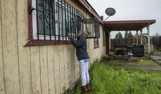 In this March 20, 2018 photo, Lashunda Britt, a cousin of Stephan Clark stands near where he was fatally shot by police in Sacramento, Calif. Relatives, activists and Sacramento officials are questioning why police shot at an unarmed black man 20 times, killing him, when he turned out to be holding only a cellphone in his grandparents' backyard. (Renee C. Byer/The Sacramento Bee via AP)