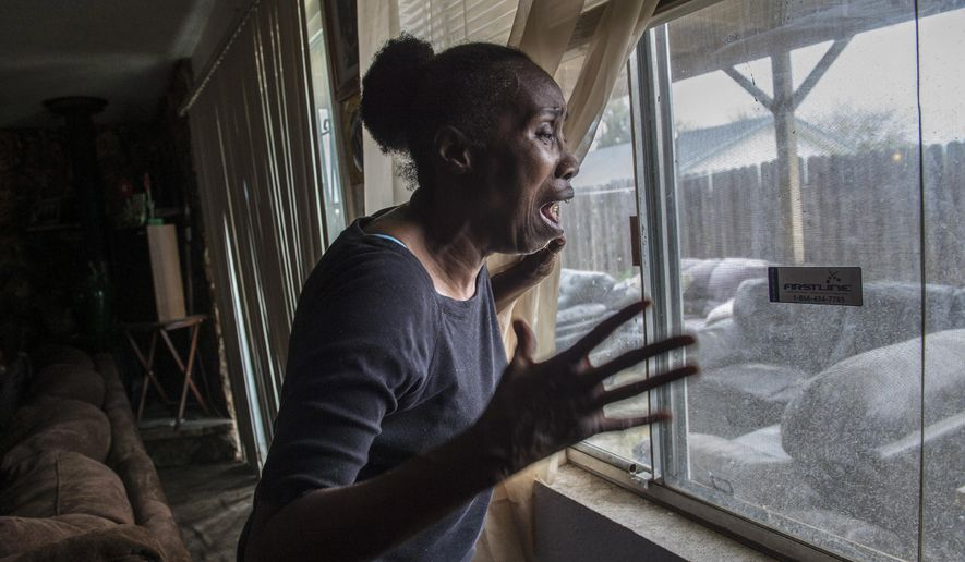 In this March 20, 2018, photo, Sequita Thompson, recounts the horror of seeing her grandson Stephan Clark dead in her backyard after he was shot by police in Sacramento, Calif. Relatives, activists and Sacramento officials are questioning why police shot at an unarmed black man 20 times, killing him, when he turned out to be holding only a cellphone in his grandparents' backyard. (Renee C. Byer/The Sacramento Bee via AP)