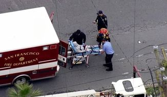 In this frame from video provided by KTVU-TV, San Francisco firefighters and police offices place a wounded person in an ambulance after a shooting that left an officer and a suspect wounded outside a pharmacy in the city's Mission District Wednesday, March 21, 2018. The San Francisco Chronicle reported that the officer and a suspect were each shot in the leg during a shootout at about 4:20 p.m. (KTVU-TV via AP)