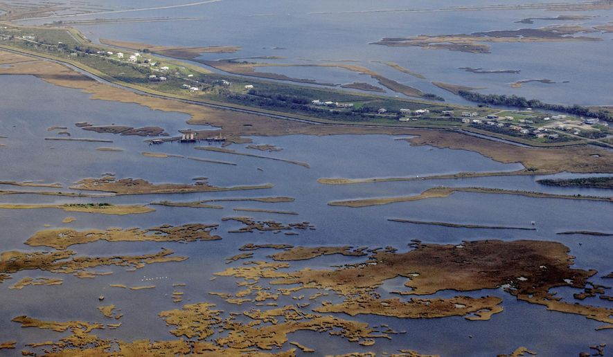 FILE- This Feb. 14, 2017 file photo shows Isle de Jean Charles, La. Louisiana officials say residents of the tiny, shrinking island are a step closer to a new home. The Louisiana Office of Community Development said Tuesday, March 20, 2018, that it has started the process of buying a 515-acre tract of high ground near Schriever in northern Terrebonne Parish for $11.7 million. The land will house dozens of Isle de Jean Charles residents whose home has experienced a 98 percent land loss since 1955 as a result of climate change. (Sophia Germer /The Advocate via AP, File)