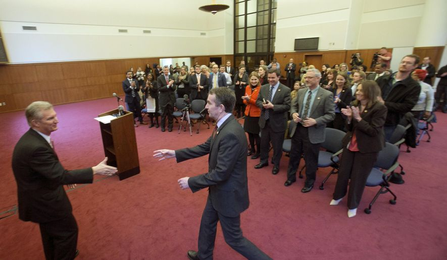 Virginia Gov. Ralph Northam, center, reaches to shake the hand of Sec. of Finance, Aubrey Lane, left, as he arrives to deliver remarks on a proposed budget for the April 11th special session during a news conference at the Capitol in Richmond, Va., Wednesday, March 21, 2018. (AP Photo/Steve Helber)