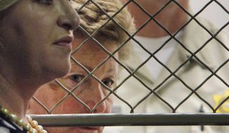 FILE - This Aug. 24, 2012 file photo shows Lois Goodman with her attorney, Allison Triessl, left, during an arraignment on murder charges in Los Angeles. A Los Angeles tennis umpire arrested before a U.S. Open match and charged in her elderly husband's 2012 death is trying to clear her name. Lois Goodman's attorneys are expected to tell jurors Wednesday, March 21, 2018, in federal court that the Los Angeles coroner's office deprived her civil rights by falsifying an autopsy report. (AP Photo/Nick Ut, File)