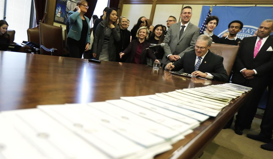A long line of bills are placed on a table in the Governor's conference room at the Capitol in Olympia, Wash., Wednesday, March 21, 2018, as Washington Gov. Jay Inslee, center right, begins a signing ceremony. Among other measures, Inslee signed a package of bills meant to address sexual misconduct at the workplace in the wake of a national conversation about sexual harassment sparked by the #MeToo movement. (AP Photo/Ted S. Warren)