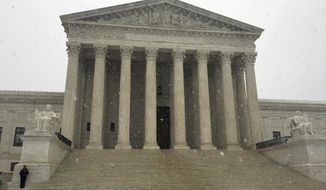 The Supreme Court begins to receive a Spring snow fall, Wednesday morning, March 21, 2018 in Washington.  Although the court is open for business today, the coming spring nor'easter caused the federal government to close its offices in the Washington area. (AP Photo/Jessica Gresko)