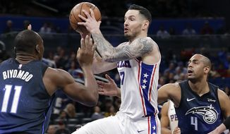Philadelphia 76ers' JJ Redick, center, looks to pass the ball as he gets between Orlando Magic's Bismack Biyombo (11) and Arron Afflalo (4) during the first half of an NBA basketball game, Thursday, March 22, 2018, in Orlando, Fla. (AP Photo/John Raoux)