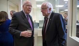 Senate Appropriations ranking member Patrick Leahy, D-Vt., left, confers with Senate Budget Committee Ranking Member Bernie Sanders, I-Vt., just before a news conference where Senate Democrats criticized President Donald Trump's tax cuts and insist on putting government funds toward a $1 trillion infrastructure package, at the Capitol in Washington, Wednesday, March 7, 2018. (AP Photo/J. Scott Applewhite)