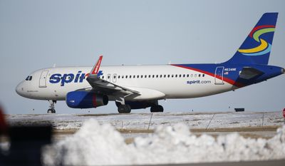 In this photograph taken late Monday, Feb. 8, 2016, a Spirit Airlines craft waits to take off from a runway at Denver International Airport. (AP Photo/David Zalubowski)
