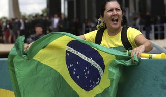 "A woman waves a Brazilian flag outside the Supreme Court in favor of arresting former Brazilian President Luiz Inacio Lula da Silva in Brasilia, Brazil, Thursday, March 22, 2018. Da Silva launched a book last week in which he says he is ""ready"" to go to jail and serve a 12-year and one-month sentence on a corruption charge conviction. (AP Photo/Eraldo Peres)"