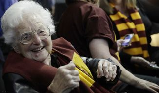 Sister Jean Dolores Schmidt sits with other Loyola-Chicago fans during the first half of a regional semifinal NCAA college basketball game against Nevada, Thursday, March 22, 2018, in Atlanta. (AP Photo/David Goldman) ** FILE **