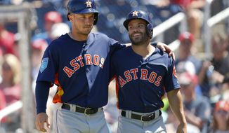 Houston Astros' Jose Altuve, right, and Alex Bregman walk to the dugout after scoring on a two-run base hit by Marwin Gonzalez in the fourth inning of a spring training baseball game against the Washington Nationals, Wednesday, March 21, 2018, in West Palm Beach, Fla. (AP Photo/John Bazemore)