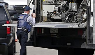 A robot is prepared for use at the scene of Walnut and 2nd Street in Pflugerville, Texas, on Wednesday, March 21, 2018 where Austin, Texas bombing suspect Mark Anthony Conditt lived. As a SWAT team closed in, the suspected bomber whose deadly explosives terrorized Austin for three weeks used one of his own devices to blow himself up early Wednesday. (Tom Reel/The San Antonio Express-News via AP)