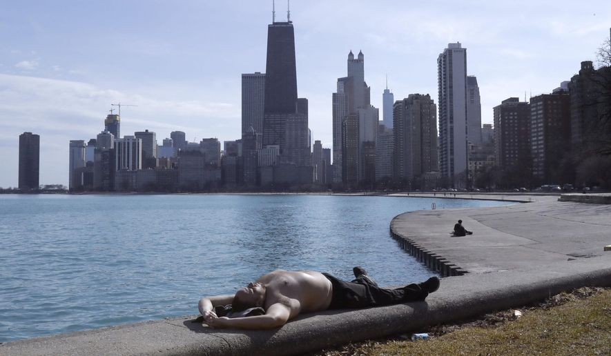 FILE - In this Feb. 27, 2018 file photo, Johnny Perez suns himself in springlike temperatures along Lake Michigan in Chicago. Congressional leaders are rejecting President Donald Trump's effort to kill or sharply cut funding of programs to protect and restore some of the nation's prized waters, such as the Great Lakes and Chesapeake Bay. (AP Photo/Charles Rex Arbogast File)