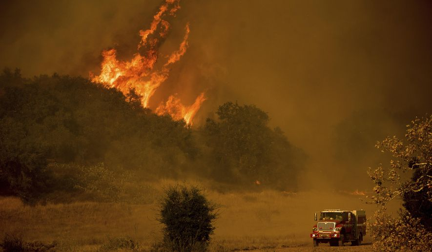 FILE - In this Dec. 9, 2017 file photo, a fire engine passes flames as a wildfire burns along Santa Ana Road near Ventura, Calif. A spending bill slated for a vote in Congress includes a bipartisan plan to create a wildfire disaster fund to help combat increasingly severe wildfires that have devastated the West in recent years. The bill sets aside more than $20 billion over 10 years to allow the Forest Service and other federal agencies end a practice of raiding non-fire-related accounts to pay for wildfire costs that approached $3 billion last year.(AP Photo/Noah Berge, Filer)