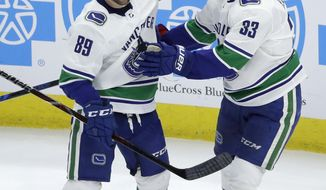 Vancouver Canucks' Henrik Sedin (33) celebrates his goal with Sam Gagner during the first period of an NHL hockey game against the Chicago Blackhawks, Thursday, March 22, 2018, in Chicago. (AP Photo/Charles Rex Arbogast)