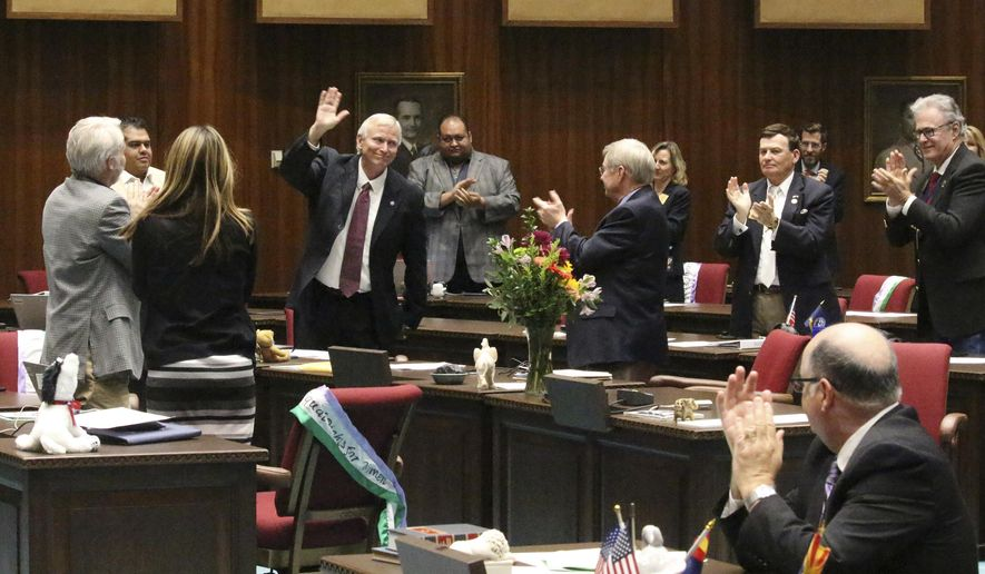 Arizona Republican Rep. Doug Coleman waves in Phoenix, Ariz., Thursday, March 22, 2018, as he gets a standing ovation from GOP and Democratic members as the House passes a 20-year extension of a sales tax that pumps $500 million a year into the state's K-12 public schools. Coleman sponsored the measure, which was seen as having little hope but passed with just 10 of 90 state lawmakers opposed on Thursday. (AP Photo/Bob Christie)