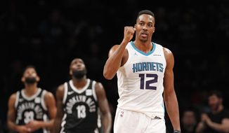 Charlotte Hornets center Dwight Howard (12) reacts during the second half of the team's NBA basketball game against the Brooklyn Nets on Wednesday, March 21, 2018, in New York. Brooklyn Nets guard Allen Crabbe (33) and forward Quincy Acy (13) watch a video replay. The Hornets won 111-105. (AP Photo/Kathy Willens) ** FILE **