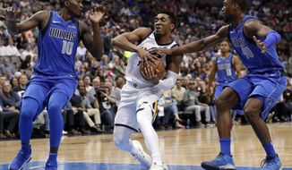 Dallas Mavericks forward Dorian Finney-Smith (10) and forward Harrison Barnes (40) defend as Utah Jazz guard Donovan Mitchell (45) fights to maintain control of the ball on a drive to the basket during the second half of an NBA basketball game Thursday, March 22, 2018, in Dallas. (AP Photo/Tony Gutierrez)