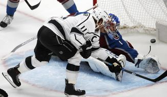 Los Angeles Kings center Anze Kopitar, front, scores a goal past Colorado Avalanche goaltender Semyon Varlamov in the first period of an NHL hockey game Thursday, March 22, 2018, in Denver. (AP Photo/David Zalubowski)