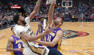 Los Angeles Lakers center Brook Lopez (11) and New Orleans Pelicans forward Anthony Davis battle under the basket in the first half of an NBA basketball game in New Orleans, Thursday, March 22, 2018. (AP Photo/Gerald Herbert)