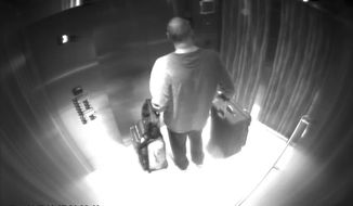 In this Sept. 25, 2017, security camera image released by MGM Resorts, Stephen Paddock stands with his luggage in an elevator at the Mandalay Bay hotel in Las Vegas. The newly released video shows the man who killed 58 people on the Las Vegas Strip moving around a casino before the attack, gambling, bringing suitcases into his room at Mandalay Bay but doing nothing that would obviously raise suspicions. (MGM Resorts via AP)