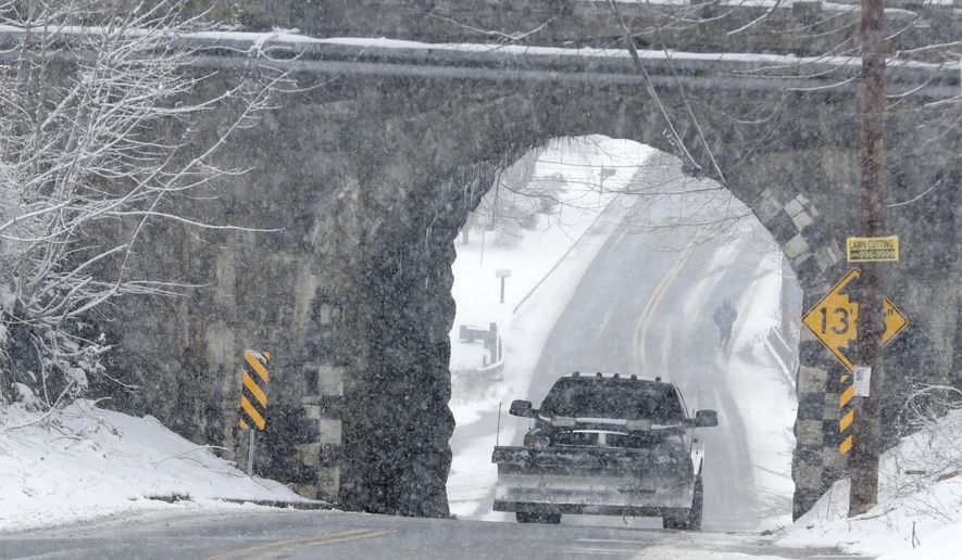 A plow makes its way under a railroad bridge as light snow falls during a snowstorm, Wednesday, March 21, 2018, in Lebanon, N.J. A spring nor'easter targeted the Northeast on Wednesday with strong winds and a foot or more of snow expected in some parts of the region. (AP Photo/Julio Cortez)