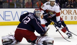 Columbus Blue Jackets goalie Sergei Bobrovsky, left, of Russia, stops a shot in front of Florida Panthers forward Aleksander Barkov, of Finland, during the first period of an NHL hockey game in Columbus, Ohio, Thursday, March 22, 2018. (AP Photo/Paul Vernon)