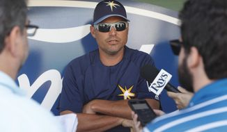 FILE - In this Feb. 24, 2018, file photo, Tampa Bay Rays manager Kevin Cash speaks to reporters before a spring training baseball game against the Boston Red Sox, in Fort Myers, Fla. The young Tampa Bay Rays feel they have a chance to be more competitive than an offseason of trimming salary might suggest.  Proving it in the rugged AL East figures to be difficult, however manager Kevin Cash likes the idea that some people are already counting his team out. (AP Photo/John Minchillo, File)
