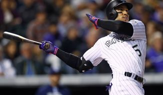 FILE - In this Sept. 16, 2017, file photo, Colorado Rockies' Carlos Gonzalez follows the flight of his two-run home run off San Diego Padres starting pitcher Jordan Lyles in the fifth inning of a baseball game in Denver.  The team brought back popular clubhouse leader Carlos Gonzalez on a one-year deal. (AP Photo/David Zalubowski, File)