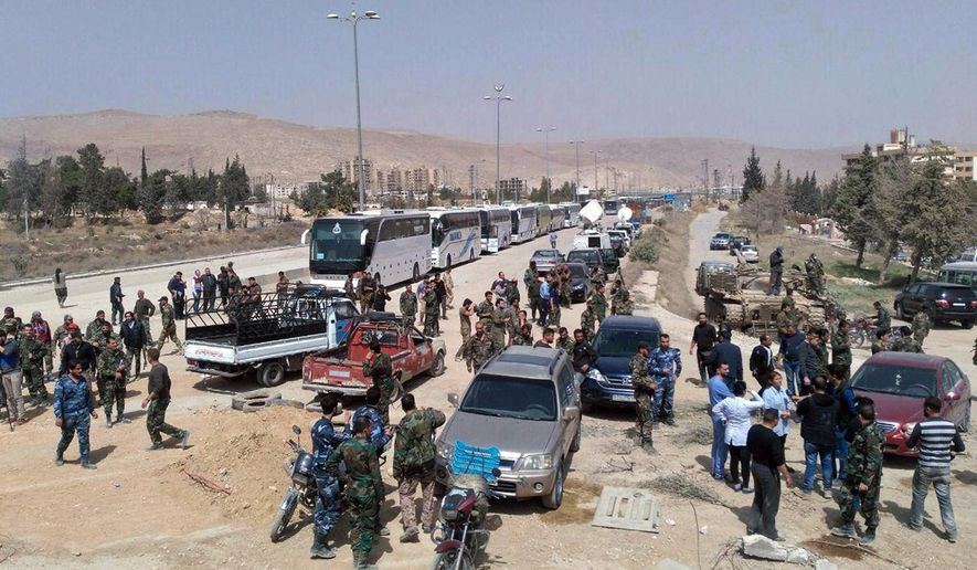 In this photo released by the Syrian official news agency SANA, Syrian government forces oversee the evacuation by buses of rebel fighters and their families, at a checkpoint in eastern Gouta, Syria, Thursday March, 22, 2108. Syrian rebels and their families were leaving in an evacuation deal that will see the town handed over to the government following years of siege. (SANA via AP)