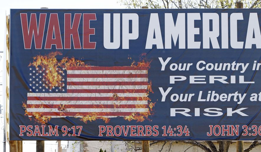 """This Wednesday, March 21, 2018, file photo shows one of two billboards displaying the Ten Commandments and a flaming American flag which Wayne Wallace installed without proper permits in Brookhaven, Miss Wallace is required to move the signs further back from their current position from state highway 51, and that's OK with Brookhaven Mayor Joe Cox, who says the city was never """"against the word of God."""" (AP Photo/Rogelio V. Solis) ** FILE **"""