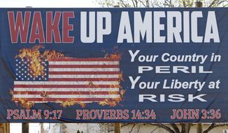 "This Wednesday, March 21, 2018, file photo shows one of two billboards displaying the Ten Commandments and a flaming American flag which Wayne Wallace installed without proper permits in Brookhaven, Miss. Wallace is required to move the signs further back from their current position from state highway 51, and that's OK with Brookhaven Mayor Joe Cox, who says the city was never ""against the word of God."" (AP Photo/Rogelio V. Solis) ** FILE **"