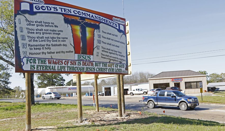 "This Wednesday, March 21, 2018 photo shows billboards displaying the Ten Commandments and a flaming American flag which Wayne Wallace installed without proper permits in Brookhaven, Miss. Wallace is required to move the signs further back from their current position from state highway 51, and that's OK with Brookhaven Mayor Joe Cox, who says the city was never ""against the word of God."" (AP Photo/Rogelio V. Solis)"