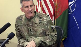 FILE - In this March 14, 2018, file photo, Gen. John Nicholson, the top American commander in Afghanistan, speaks to reporters at Bagram Air Base north of Kabul, Afghanistan. Nicholson says America has a role to play in setting the conditions for members of the Taliban to lay down their weapons and move back into Afghanistan society. Nicholson says integration talks are already going on behind the scenes and U.S. and Afghan officials are working out a plan that will lay out how the U.S. will support the peace effort. (AP Photos/Robert Burns, File)