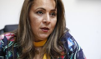In this, Monday, March 12, 2018 photo, Helene Villalonga speaks during an interview at AMAVEX INC., an organization she founded that helps reunify migrant families and victims of domestic violence find shelter, in Doral, Fla. People who study immigrant trends in the United States says the Venezuelans seem to be following a similar path as the Cubans who fled the revolution in 1959 and the upheaval that followed. (AP Photo/Wilfredo Lee)
