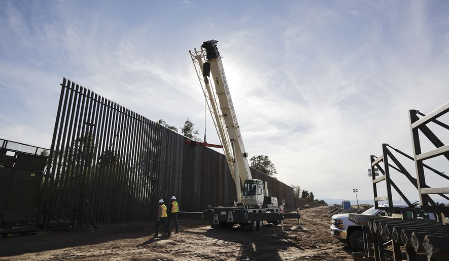 In this March 5, 2018, photo, construction continues on a new, taller version of the border structure in Calexico, Calif. Congress gave President Donald Trump the $1.6 billion he sought for one year of funding of the border wall with Mexico, but he wanted a long-term wall financing commitment. (AP Photo/Gregory Bull)