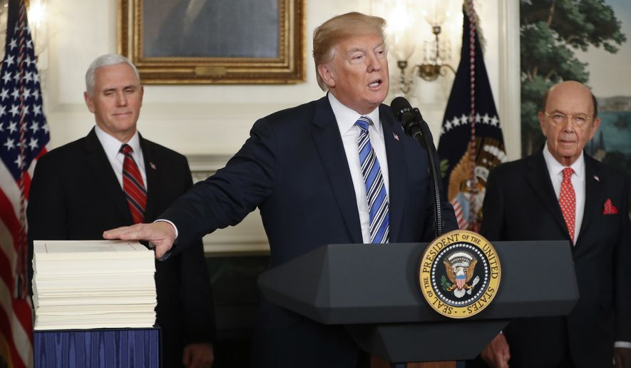 President Donald Trump reaches to touch a copy of the $1.3 trillion spending bill as he speaks in the Diplomatic Room of the White House in Washington, Friday, March 23, 2018, as Vice President Mike Pence, left, and Commerce Secretary Wilbur Ross watch. (AP Photo/Pablo Martinez Monsivais)