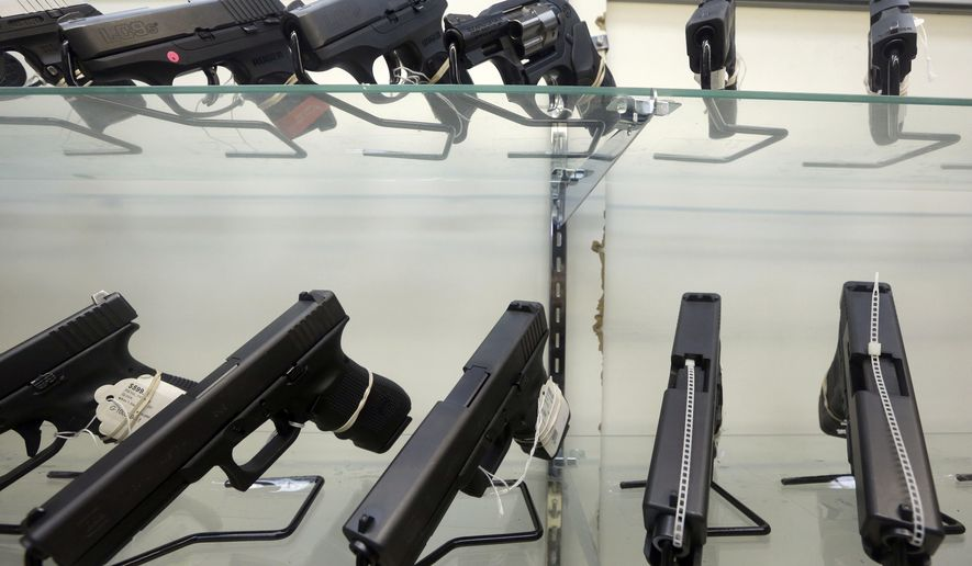 This June 29, 2016, file photo shows guns on display at a gun store in Miami. (Associated Press) ** FILE **