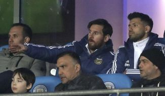 Lionel Messi, centre, and Sergio Aguero are seen in the stands during the international friendly soccer match between Argentina and Italy at the Etihad Stadium in Manchester, England, Friday March 23, 2018. (Martin Rickett/PA via AP)