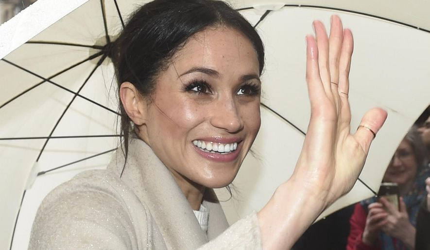 Meghan Markle shelters from the rain under an umbrella as she waves to wellwishers during a walkabout in Belfast  with Prince Harry, after a visit to the Crown Bar in the city centre on  Friday March 23, 2018. Prince Harry and Meghan Markle  will be married at St. George's Chapel in Windsor Castle on May 19.(Joe Giddens/PA via AP)