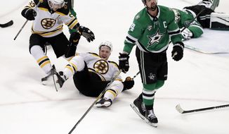 Boston Bruins' Brad Marchand (63) skates over to celebrate a goal with David Pastrnak, bottom, as Dallas Stars left wing Jamie Benn (14) skates away from the celebration late in the third period of an NHL hockey game in Dallas, Friday March 23, 2018. Stars goalie Kari Lehtonen, rear, lies on the ice. (AP Photo/Tony Gutierrez)