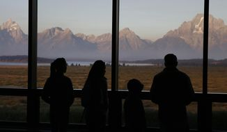 FILE - In this Aug. 28, 2016 file photo visitors watch the morning sun illuminate the Grand Tetons from within the Great Room at the Jackson Lake Lodge, in Grand Teton National Park, north of Jackson Hole, Wyo. An environmental group says Grand Teton National Park is inappropriately keeping the public from hearing about plans for several new cellphone towers at the foot of the Teton Range. The group Public Employees for Environmental Responsibility, or PEER, says it obtained a document through the Freedom of Information Act showing Grand Teton has at least tentative plans for 55 miles of fiber-optic cable and new cellphone towers at 11 specific locations. (AP Photo/Brennan Linsley,File)