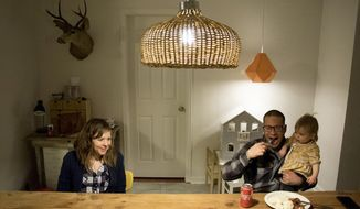 In this Wednesday, March 14, 2018, photo, Kimberly Hyde sits at her kitchen table with her roommate, John Muir, and her daughter, Ruby, in the home they share with other roommates in Denver. (Kevin J. Beaty/Denverite via AP)